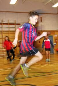 This image depicts a young student in a blue and red jersey running in the gym with friends